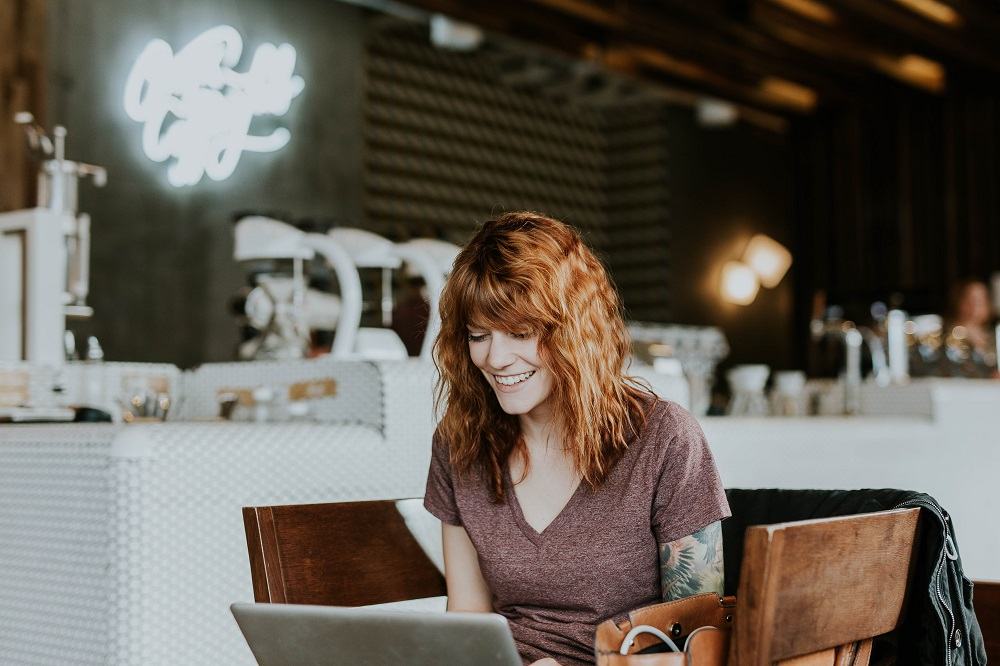 A woman smiling while looking at a laptop screen at a coffee shop